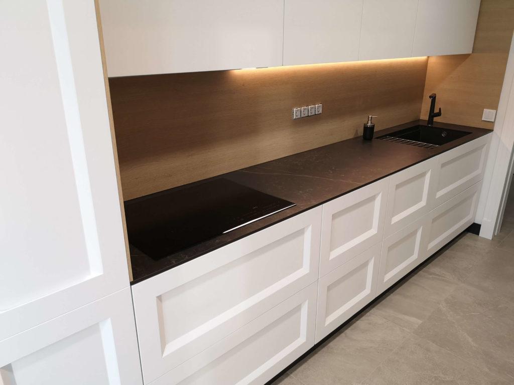 En esta cocina vemos la mezcla de estilos, con un diseño «minimal» sin tiradores y lineal, pero utilizando una puerta de molduras tipo clásico en la parte baja, encimera Dekton negra con vetas tipo mármol y paneles en madera forrando las paredes.