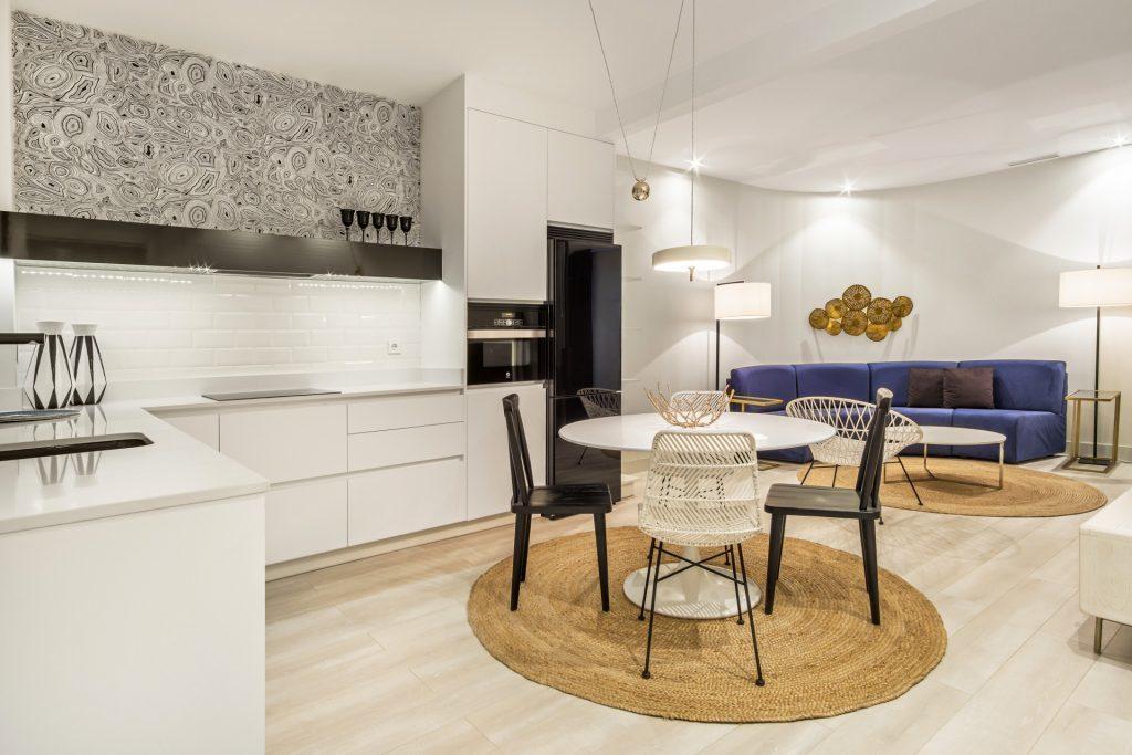 Cocina abierta al salón con electrodomésticos integrados y en cristal negro. Lámpara y mobiliario auxiliar de diseño
