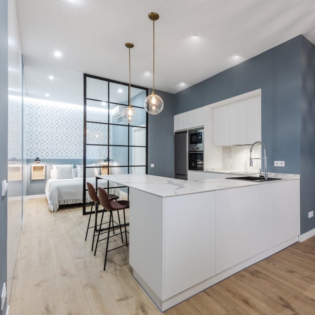 Esta cocina abierta al salón presenta una gran mesa que podrá ser usada como encimera de cocina, mesa de comedor o trabajar con el ordenador / hacer los deberes.